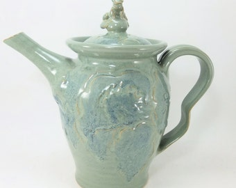 green teapot with a frog