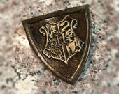 Hogwarts school pin. Dark leather w/gold highlights.