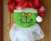 GRINCH CHRISTMAS  WREATH made with a green deco mesh face  with a red mesh santa hat with snowflakes and a white mesh collar