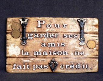 The house doesn't do credit. French saying plate. Words to live by.