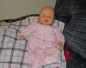 13 inch baby doll with cloth body and plastic head, arms and legs.  Includes 3 outfits.