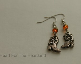 Silver cowboy boot earrings with burnt orange crystals.\