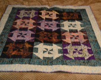 Quilted wall hanging or lap quilt. Machine pieced and quilted in beautiful purple, turquoise, white, brown, yellow, and pink batiks