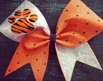 holo orange glitter and white (silver)  fabric cheer bow with paw and black rhinestones.Ask about bulk discounts, color and mascot options.