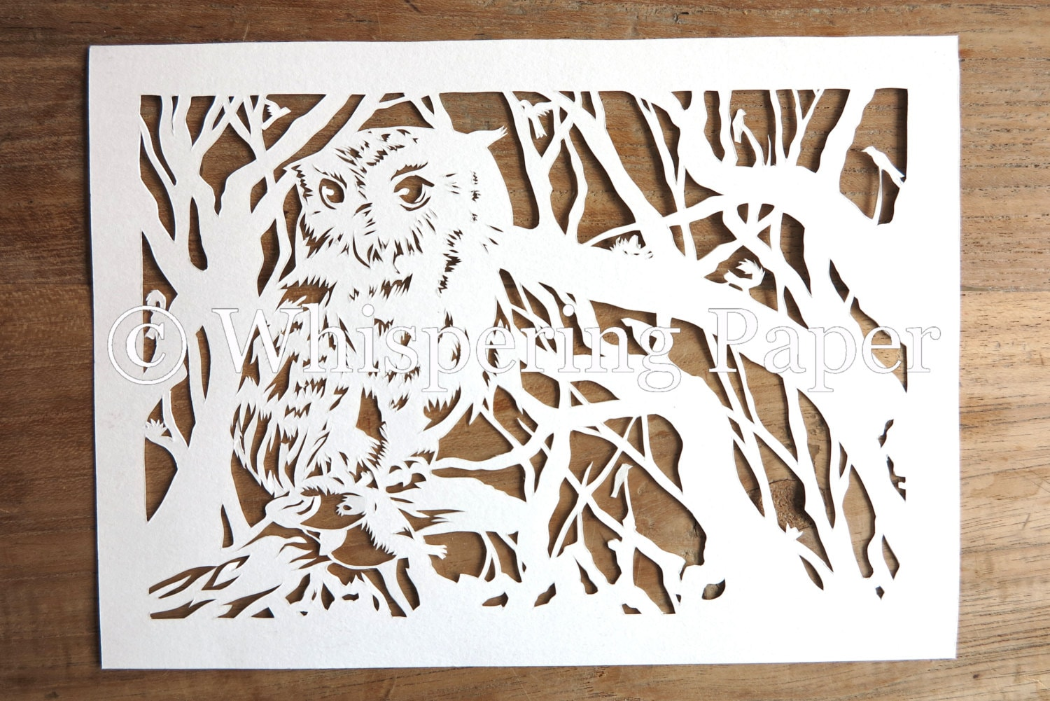 Hand cut paper cut art of an owl in vivacious forest
