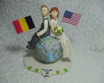 Personalized bride and groom sitting on the globe wedding cake topper