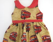 London bus dress dress on tan print fabric with a red with white spots collar and sash.