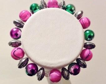 Bracelet. 17cm Features two/tone Fancy Glass beads. Pink enamelleg Glass/ Black swirly patterns