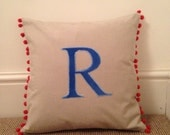 Bright colourful cushionpillowdesigner fabric with applique letter and red pom pom trim.