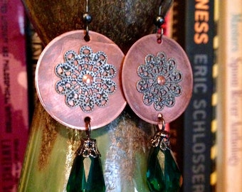 A handmade set of boho inspired oxidized copper metal earrings with silver filigree accents and a green dangling bead.
