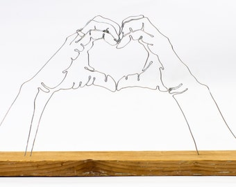 Hands make a heart wire art sculpture
