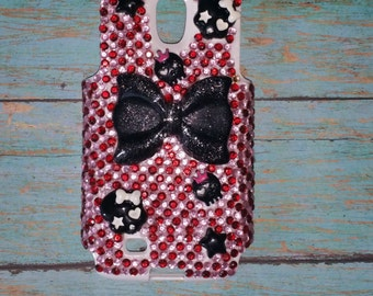 Red and pink rhinestone covered bling phone case with bows stars and skulls