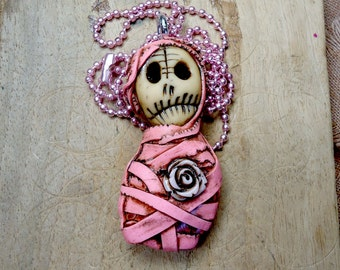 CASILDA, ugly girly mummy bandaged in pink with a dirty rose on her heart. Creepy pendant with metal ball chain