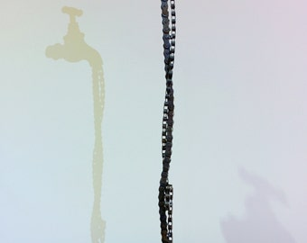 Faucet. Metal sculpture with bicycle and motorcycle chains.