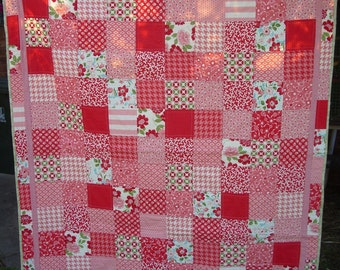 Handmade modern quilt using pink, red and green fabric from 'Bonnie & Camille'