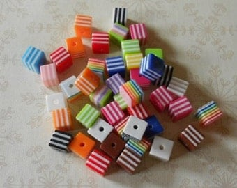 A pack of 25 colourful striped cube resin beads