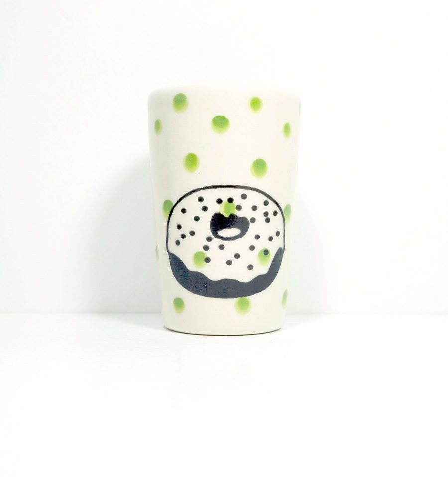 itty bitty cylinder with a donut on leaf green polkadots, ready to go.