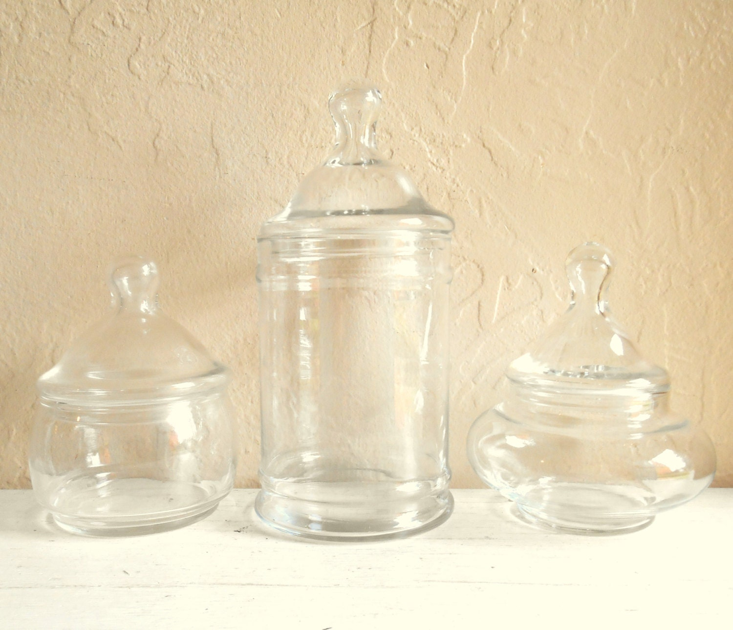 Trio of vintage glass apothecary jars with lids centerpiece