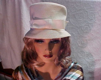 White faux straw cloche hat with white grossgrain ribbon going around the crown- bow in front- fits 21 1/2