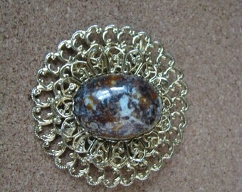 Round gold tone filigree brooch pin with brown marble cab center