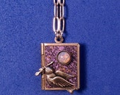 Dove Love Locket, purple and silver, holding 14 ways to tell someone you love them, from English to American Sign Language.