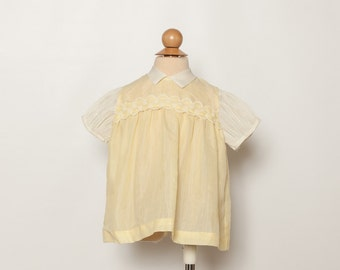 vintage 1950s baby girl's dress in pale yellow