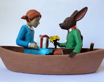 Brown rabbit and red haired girl sailing away. Ceramic boat sculpture one of a kind clay art.