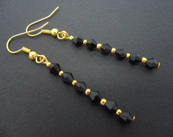 A pair of hand made gold plated black crystal dangly earrings.