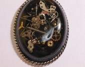 Steampunk on black in a metal setting pendant steampunk pendant gears watch parts resin steampunk necklace gears in resin oval pendant