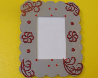 Gray picture frame with red embellished designs