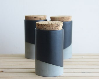 Ceramic jar with cork lid in gray with black matte glaze.