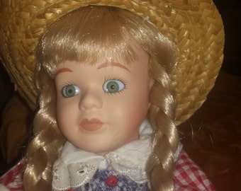 Sweet little porcelain country doll.  She is flawless up to her sweet hat.