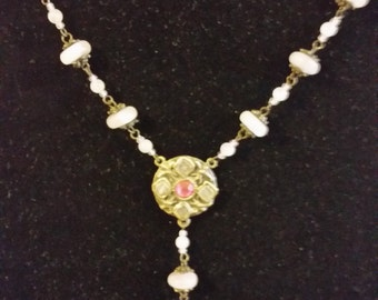 16 inch gold tone necklace with pink stones with a drop from the center.