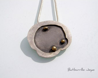 Texturized sterling silver with bronze pendant.  Black pendant with bronze details