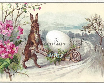 Antique Easter postcard of a brown bunny rabbit pushing a cart with a giant white egg in the snow with pink flowers INSTANT download