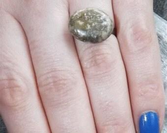 Polished Isle of Wight pebble on adjustable black enamelled ring.