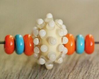Handmade lampwork glass bead, lampwork focal bead, lampwork pendant, hollow lampwork bead, ivory, white,dot, orange, turquoise blue spacers