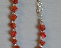 Hand beaded bracelet.  Millefiori beads in shades of orange and white, flower shapes within the glass.