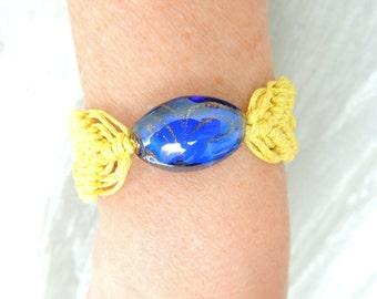 Yellow macramé bracelet and dark blue glass bead