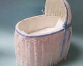 One Inch Scale, White Lace Bassinet trimmed in blue ribbons.