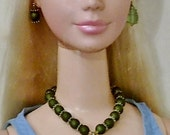 Barbie with a forest green and gold necklace. There is a wire wrapped sea glass green tear drop at the front