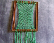 Working macramé mounted on recycled wood frame, green nylon rope net with fringe pattern, retro, bohemian, brown, upcycled, eco-friendly
