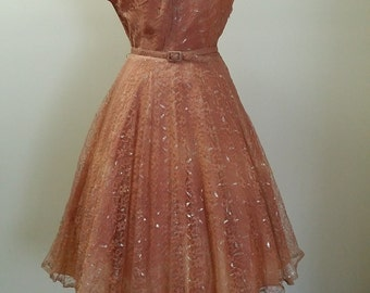 Vintage 1950's peach lace capped sleeve dress with silver leaf detail. Full skirt and original belt.