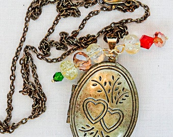 0445 - Antique brass locket, antique brass jewelry, oval locket, hearts on front, crystal beads, holds 2 photos,  Swarovski crystals,crystal