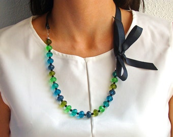Necklace with crystal beads of different colours and black bow.