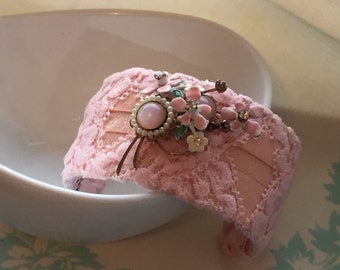 "Light Pink/peach 1 3/4"" cuff bracelet with pastel flower adornment"