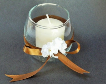 Rustic votive decorated with baby's reath and ribbon.