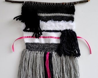 Weaving, black, gray, white and pink wall hanging on branch. Bohemian spirit. Interior decoration.