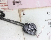 piano. heart locket necklace. in silver ox with etched lines locket
