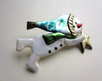 Flying Snowman with multi colored stocking cap and chartreuse green scarf holding a star pin brooch